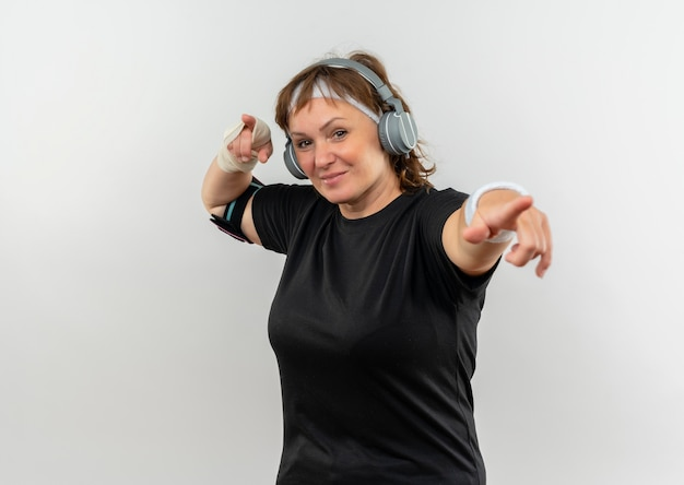 Sportliche frau mittleren alters im schwarzen t-shirt mit stirnband und kopfhörern, die sicher lächelnd zeigen, mit zeigefingern stehend über weißer wand