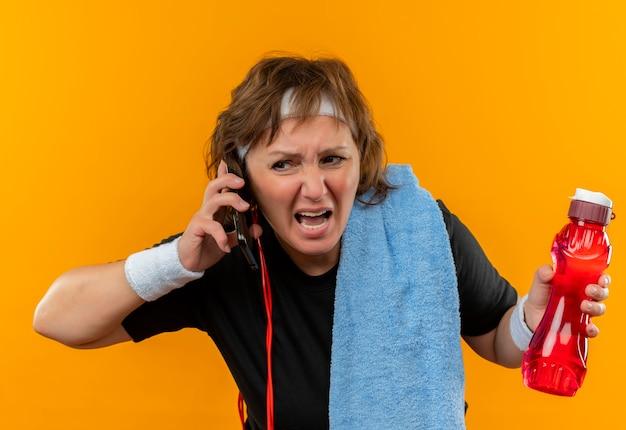 Sportliche frau mittleren alters im schwarzen t-shirt mit stirnband und mit handtuch auf der schulter, die auf handy spricht, das enttäuscht schreit und mit aggressivem ausdruck über orange wand steht