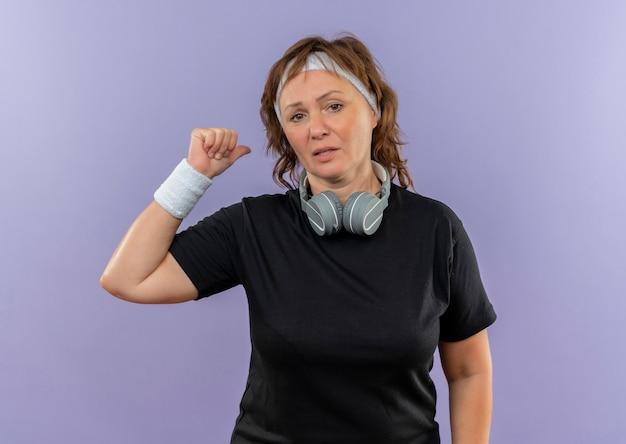Sportliche frau mittleren alters im schwarzen t-shirt mit verwirrtem stirnband, das mit dem fingerrücken zeigt, der über blauer wand steht