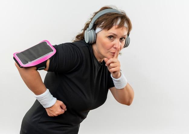 Sportliche frau mittleren alters in schwarzem t-shirt mit stirnband und kopfhörern, die schweigengeste mit finger auf lippen machen, die über weißer wand stehen