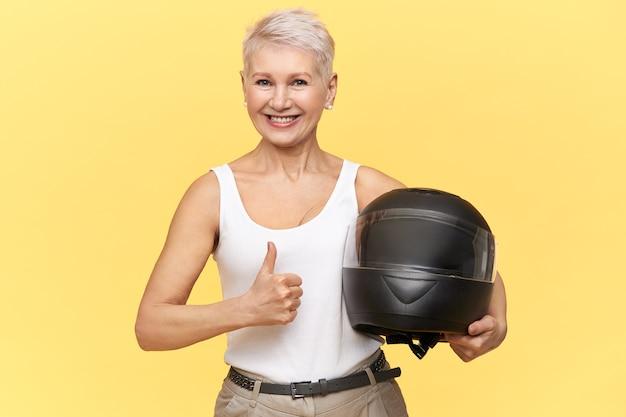 Sportliche frau mittleren alters mit blondem haar, das schützenden motorradhelm hält