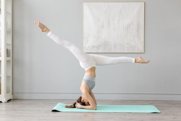 Sportliche frau praktiziert yoga zu hause handstand