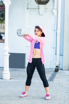Sportliche frau schwingt kettlebell
