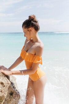 Sportliche frau trägt retro-badeanzug, der seefelsen berührt. außenporträt der romantischen gebräunten dame mit niedlicher frisur, die am ozeanufer steht.