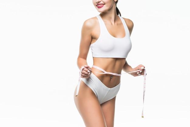Sportliche frau und messen um ihren körper isoliert auf weißer wand