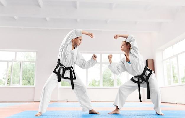 Sportliche frau zwei, die am karatetraining in der kampfkunstschule kämpft.