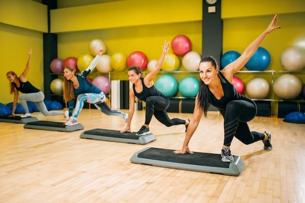Sportliche frauen in sportbekleidung auf schritt aerobic workout indoor. weibliche sportteamarbeit im fitnessstudio. fit klasse, fitnessübung in bewegung