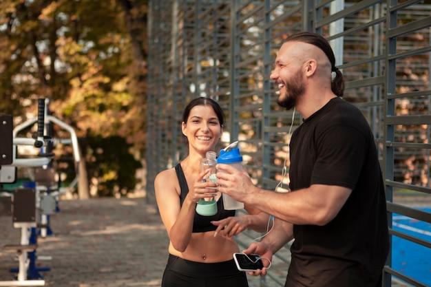 Sportliche freunde machen eine pause, um feuchtigkeit zu trinken