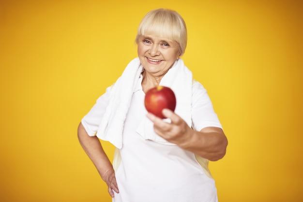 Sportliche großmutter bietet apfel-übungs-nahrung an.