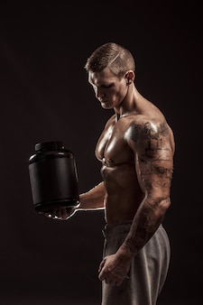 Sportliche hintergründe. starker bodybuilder, der ein plastikglas mit einem isolierten trockenen protein hält. sportessen
