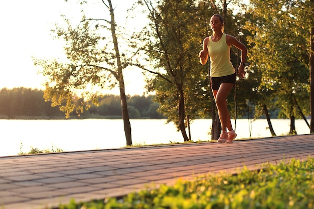 Sportliche joggerin, die draußen in der natur läuft und trainiert.