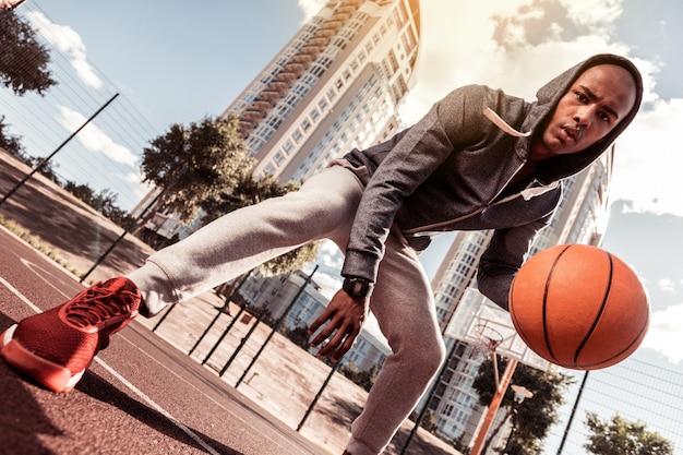 Sportliche jugend. niedriger winkel eines netten jungen mannes, der sie beim basketballspielen ansieht