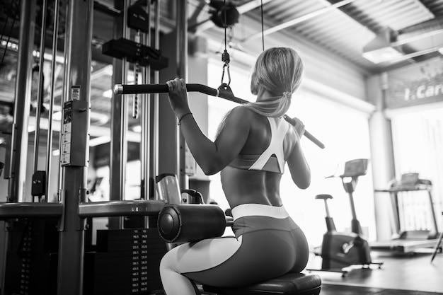 Sportliche junge fitnessfrau, die im fitnessstudio ausübt