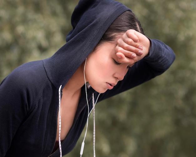 Sportliche junge frau der nahaufnahme erschöpft nach dem training
