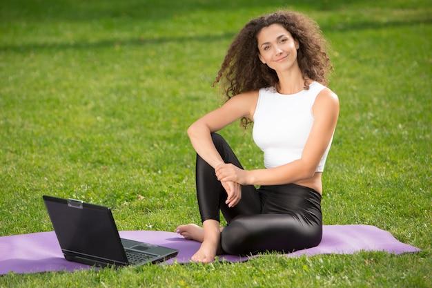 Sportliche junge frau, die auf dem gras mit laptop sitzt
