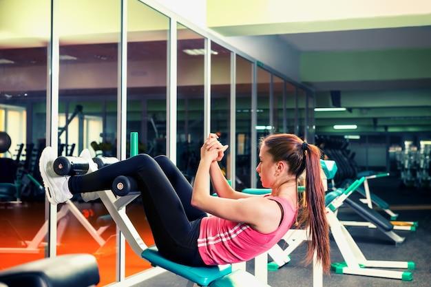 Sportliche junge frau, die bauchmuskeltraining unter verwendung der trainingsvorrichtung in einem fitnessstudio tut