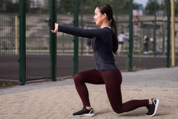 Sportliche junge frau, die draußen trainiert
