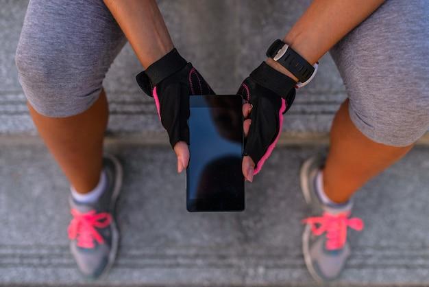Sportliche junge frau, die ein telefon verwendet