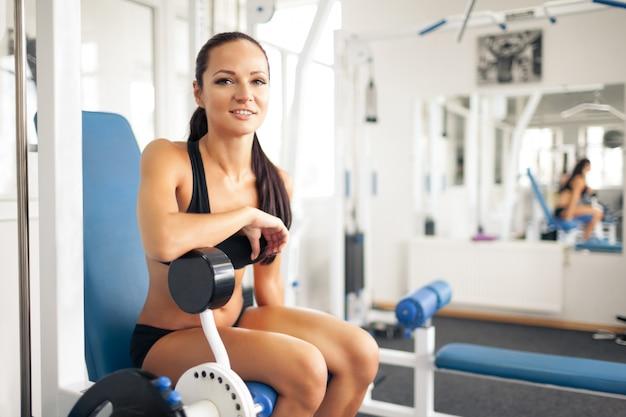 Sportliche junge frau, die im fitnessstudio aufwirft.