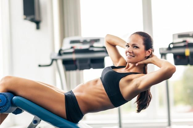 Sportliche junge frau, die im fitnessstudio trainiert.