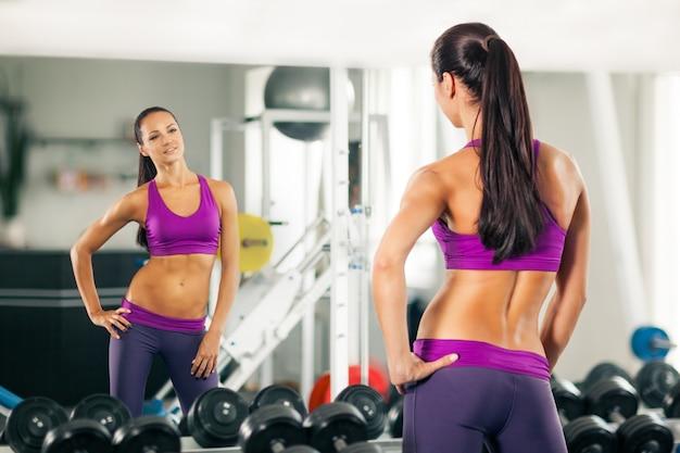 Sportliche junge frau, die im spiegel schaut.