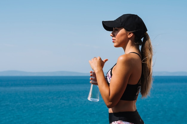 Sportliche junge frau, die in der hand nahe dem meer hält die wasserflasche weg schaut steht
