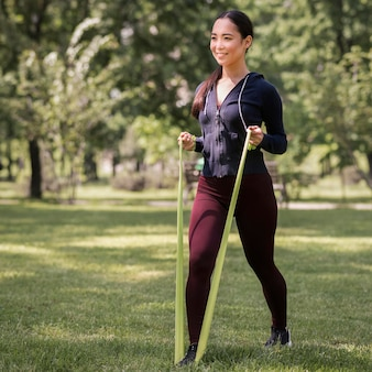 Sportliche junge frau, die mit gummiband trainiert