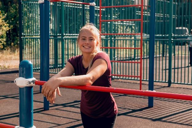 Sportliche junge frau, die nach dem training auf dem sportplatz steht und in die kamera schaut und lächelt