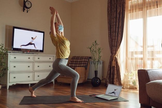 Sportliche junge frau, die online yogastunden nimmt und zu hause übt, während sie in quarantäne ist. konzept des gesunden lebensstils, des wohlbefindens, der sicherheit während der coronavirus-pandemie, auf der suche nach einem neuen hobby.