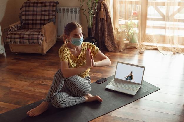 Sportliche junge frau, die online yogastunden nimmt und zu hause übt, während sie in quarantäne ist.