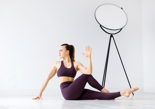 Sportliche junge frau, die twist-stretching-übungen auf dem boden in einem high-key-fitnessstudio in einer gesundheit macht