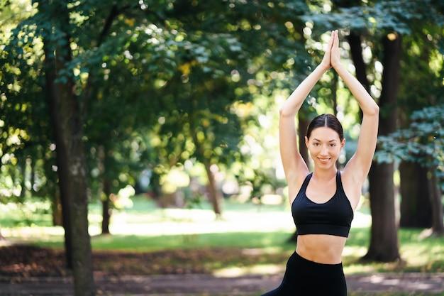 Sportliche junge frau, die yoga im park am morgen tut