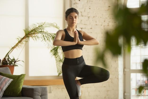 Sportliche junge frau, die yoga-lektionen online nimmt und zu hause übt