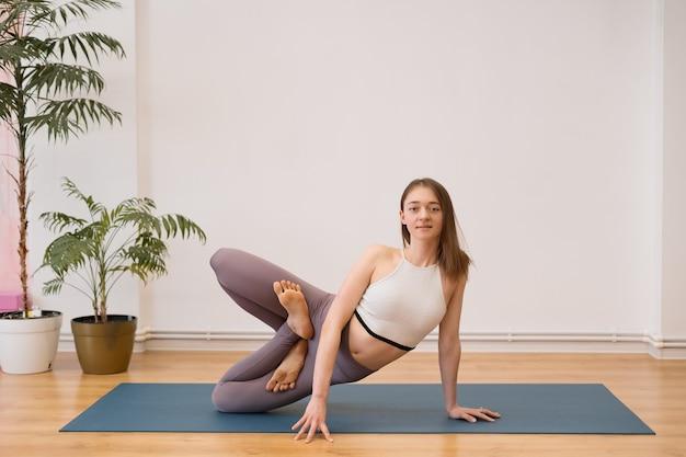 Sportliche junge frau, die yoga-praxis auf weißer wand mit pflanzen tut - konzept des gesunden lebens und des natürlichen gleichgewichts zwischen körper und geistiger entwicklung