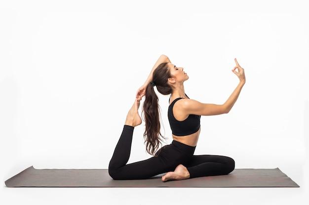 Sportliche junge frau, die yoga-praxis isoliert auf weißer oberfläche macht - konzept für gesundes leben und natürliches gleichgewicht zwischen körper und geistiger entwicklung