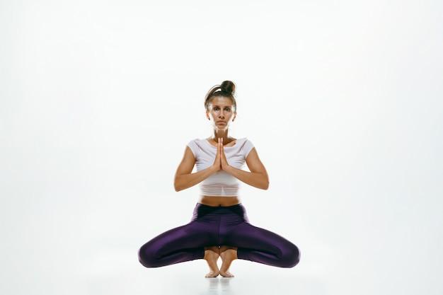 Sportliche junge frau, die yoga-praxis isoliert tut. fit flexibles weibliches modell üben. konzept eines gesunden lebensstils und eines natürlichen gleichgewichts zwischen körperlicher und geistiger entwicklung.