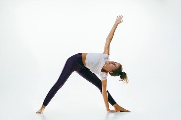 Sportliche junge frau, die yoga-praxis lokalisiert auf weiß tut
