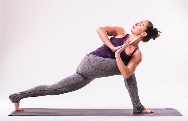 Sportliche junge frau, die yoga-praxis lokalisiert auf weißem hintergrund tut - konzept des gesunden lebens und des natürlichen gleichgewichts zwischen körper und geistiger entwicklung