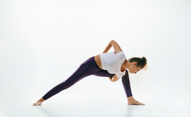 Sportliche junge frau, die yoga-praxis lokalisiert auf weißem studiohintergrund tut. fit flexibles weibliches modell üben. konzept eines gesunden lebensstils und eines natürlichen gleichgewichts zwischen körperlicher und geistiger entwicklung.