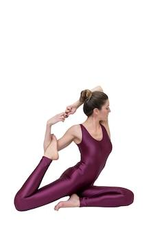 Sportliche junge frau, die yogapraxis getrennt auf weißem hintergrund tut