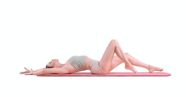 Sportliche junge frau, die yogapraxis tut. das konzept eines gesunden lebensstils und eines natürlichen gleichgewichts zwischen körper und geist. pilates, dehnung. gemischte medien