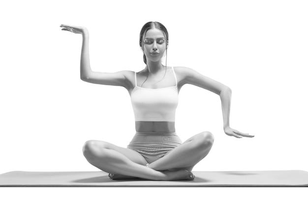 Sportliche junge frau, die yogapraxis tut. isoliert auf weißem hintergrund. das konzept eines gesunden lebensstils und eines natürlichen gleichgewichts zwischen körper und geistiger entwicklung. pilates, dehnung.