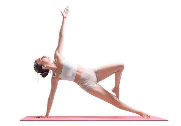 Sportliche junge frau, die yogapraxis tut. seitenplanke. isoliert auf weißem hintergrund. gemischte medien