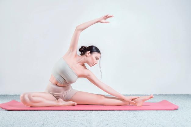 Sportliche junge frau, die yogapraxis tut. sie sitzt auf der matte und streckt sich. gemischte medien