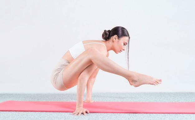 Sportliche junge frau, die yogapraxis tut. sie steht in ihren armen auf einer roten matte. gemischte medien