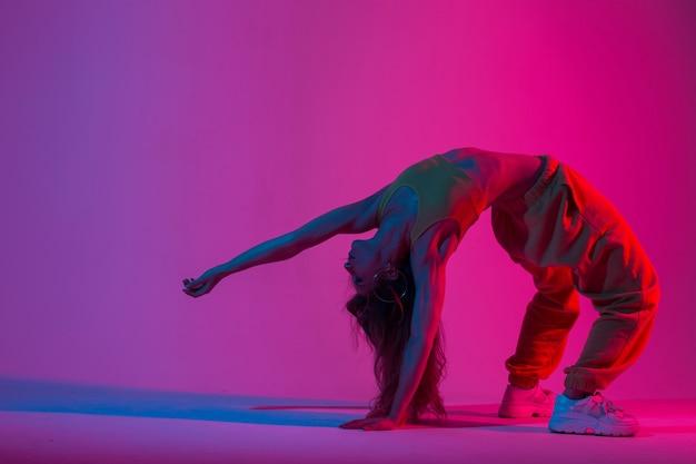 Sportliche junge frau im modischen sportanzug macht yoga-übungen in einem raum mit roter farbe im disco-stil. yogalehrerin macht fitness im studio mit einem erstaunlichen mehrfarbigen licht.