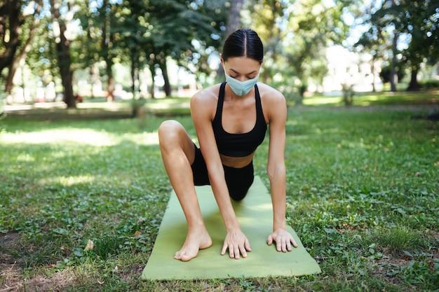 Sportliche junge frau in einer medizinischen schutzmaske, die am morgen yoga im park macht