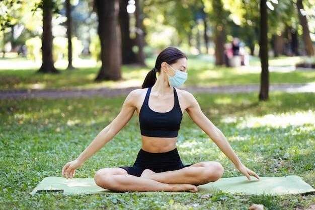 Sportliche junge frau in einer medizinischen schutzmaske, die morgens im park yoga macht, frauentraining auf einer yogamatte