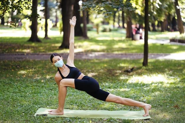 Sportliche junge frau in einer medizinischen schutzmaske, die yoga im park macht