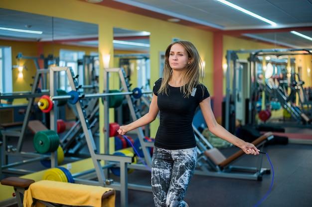 Sportliche junge frau in sportbekleidung, die mit springseil ausübt